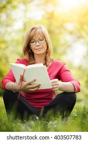 Cheerful mature woman reading a book in the park