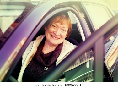 Cheerful mature woman sitting in new car at driver seat