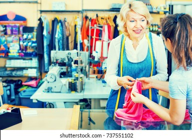 Cheerful mature woman tailor taking order from customer at a sewing workshop