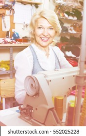 cheerful mature woman tailor using sewing machine at workshop