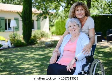 cheerful mature woman visiting her mother elderly senior female walk in retirement house hospital garden