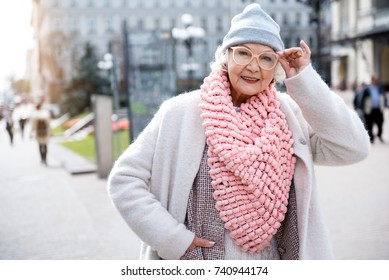 Cheerful mature woman walking in city
