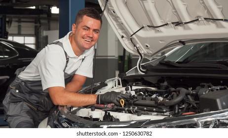 Cheerful mechanic enjoying working at the garage