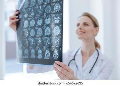 Cheerful medical specialist examining x ray at the laboratory