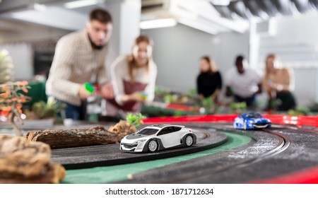 Cheerful men and women play together with a modern slot car racing track