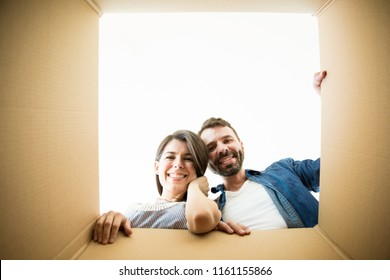 Cheerful mid adult couple looking in corrugated box in new apartment