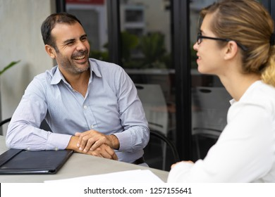 Cheerful mid adult hr manager having interview with candidate. Caucasian male manager talking to female client. Job interview or meeting concept