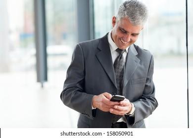 cheerful mid age businessman using smart phone