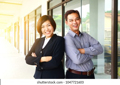 Cheerful middle aged asian businessman and businesswoman