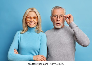 Cheerful middle aged woman and her husband pensioner reacts on shocking news keeps hand on spectacles isolated over blue background. Family age and emotions concept. Senior couple at pose home