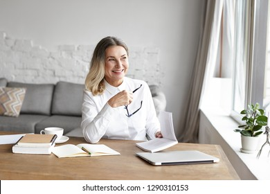 Cheerful middle aged woman smiling broadly, enjoying reading good book during small break while working distantly from home office
