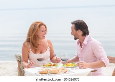 Cheerful middle-aged couple eating in the restaurant near the ocean coastline. Mature people sitting face to face and smiling.