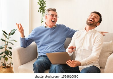 Cheerful Middle-Aged Son And Senior Father Using Laptop And Laughing Sitting On Couch At Home. Selective Focus