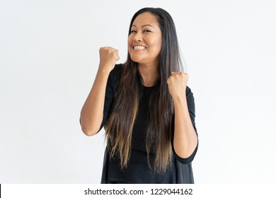 Cheerful middle-aged woman celebrating success. Lady pumping fists and looking at camera. Success concept. Isolated front view on white background.