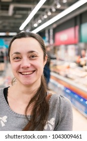 A cheerful middle-aged woman with long hair in a supermarket.