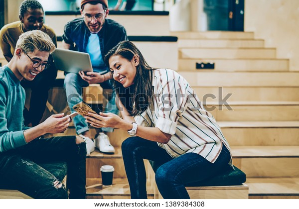 Cheerful millenial woman showing latest feed from social networks to group of multiracial friends, happy crew of male and female colleagues spending free time in college talking and using gadgets