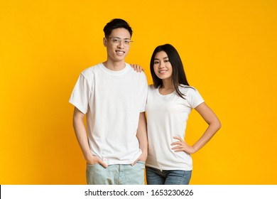 Cheerful millennial asian couple posing on yellow background together, copy space