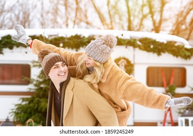 Cheerful millennial couple having fun outside at winter camping, playing and laughing together, enjoying camping during Christmas holidays. Joyful woman piggybacking boyfriend, free space