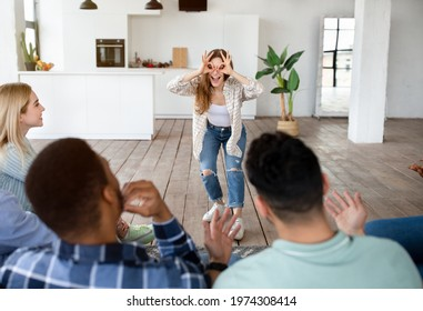 Cheerful millennial friends playing word guessing game together at home party. Funny lady using pantomime to play charades with fellow students. Domestic entertainments concept