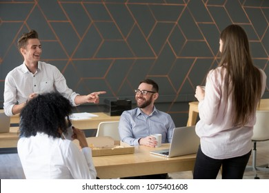 Cheerful millennial team people chatting and laughing eating pizza together, friendly diverse colleagues group talking discussing funny joke having fun during lunch or coffee break in office room
