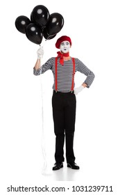 cheerful mime holding bundle of black balloons with helium isolated on white