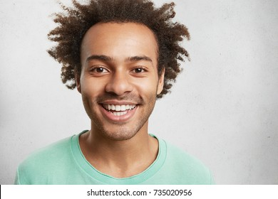 Cheerful mixed race male with bristle, bushy hairstyle and white perfect teeth, has good mood after spending weekends with friends, go together on picnic, have fun and relaxation. Happy person