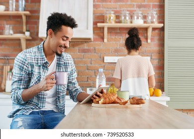 Cheerful mixed race male watches comedy on tablet, uses free internet connection, drinks coffee and eats delicious croissants. Woman stands at cooker, prepares breakfast for family in background