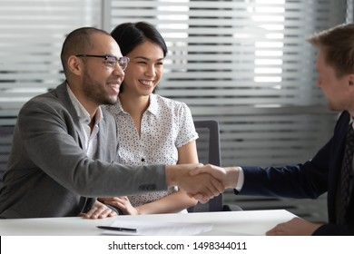 Cheerful mixed race married spouse shaking hands with financial advisor, lawyer, real estate agent, broker or bank manager after signing contract, buying insurance services, thanking for expert help.