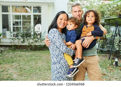 Cheerful mixed-race parent and children standing in front of their house