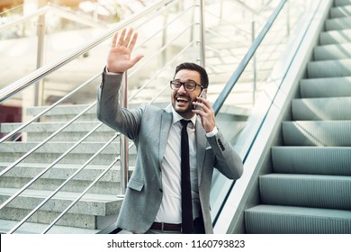 Cheerful modern busy businessman talking over cell phone and waving to his friends.