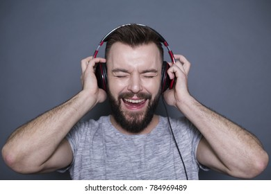 A cheerful modern smiling guy in big headphones listens to cool music on a gray background.