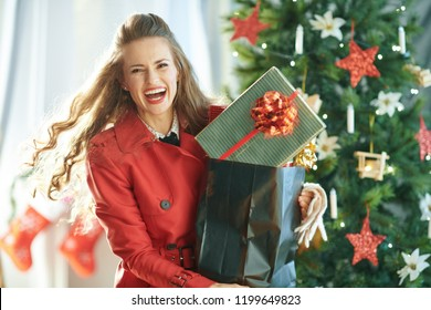 cheerful modern woman in red trench coat with shopping bag full of Christmas present boxes near Christmas tree