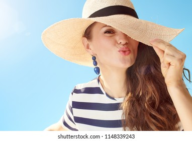 cheerful modern woman in straw hat against blue sky playing with straw hat