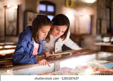 Cheerful mom and daughter looking at medieval expositions in museum