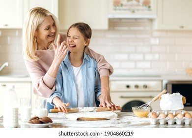 Cheerful mom or grandma and her pretty little daughter or granddaughter spend time together at the kitchen. They cook together a pie, indulge in flour, laugh and have fun