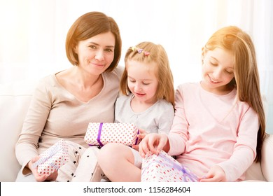 Cheerful mom and her beautiful daughters exchanging gifts Happy birthday, Happy Woman's day, Happy Mother's day, Christmas gifts. Mom and daughters unwrapping gifts