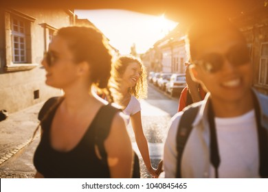 Cheerful moment of a two couples walking down the street on a golden hour.