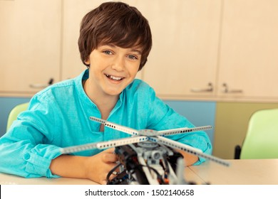 Cheerful mood. Smiling schoolboy sitting in the classroom finishing his work on helicopter model made of construction set.