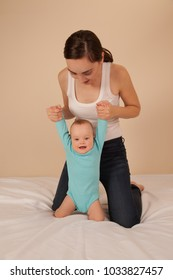 Cheerful mother with baby in blue bodysuit playing in bed and having fun
