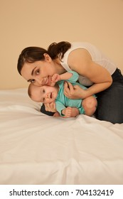 Cheerful mother with baby playing in bed