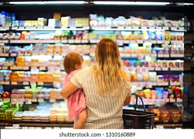 Cheerful mother and baby spending time in shopping in supermarket, shallow depth of field
