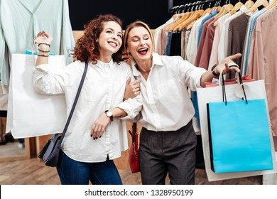 Cheerful mother. Blonde-haired mature mother feeling cheerful spending shopping time with her girl