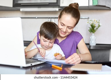 Cheerful mother cares of her son, being on maternity leave, works freelance with laptop computer, pose together at kitchen. Busy mom plays wit small boy, has rest after work. Family concept.
