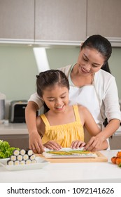 Cheerful mother and daughter making suchi rolls