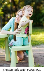 Cheerful mother and daughter in park with children's furniture