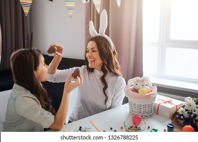 Cheerful mother and daughter prepare for Easter. They hold chocolate eggs and smile. Decoration on table. Model wear white rabbit ears.