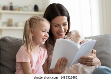 Cheerful mother and daughter sitting on couch reading interesting funny fairytale story, mom develops schoolgirl kid spending time with literature, upbringing, care and education of children concept