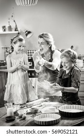 Cheerful mother with her children, a girl and a boy having fun while preparing a cake in their kitchen. They play clapping hands to project flour. Black and white picture