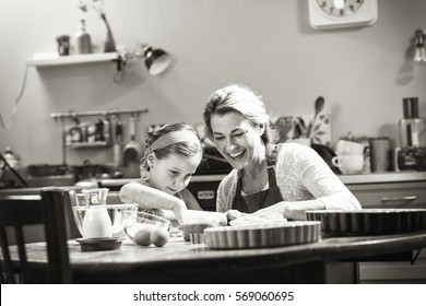 A cheerful mother and her daughter having fun while making pastry in a kitchen. Black and white