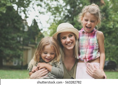 Cheerful mother with her daughters outdoor.
